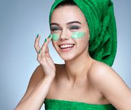 Laughing girl applying moisturizing cream on her face. Royalty Free Stock Photography