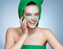 Laughing girl applying moisturizing cream on her face. Stock Photography