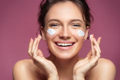 Free Laughing Girl Applying Moisturizing Cream On Her Face. Royalty Free Stock Photography - 109379277