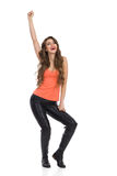 Laughing Girl With Arm Raised. Young attractive woman in black leather trousers, orange shirt and boots standing with arm raised and smiling. Full length studio Royalty Free Stock Photo