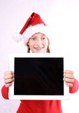 Laughing Girl as Mrs. Santa with tablet Royalty Free Stock Image
