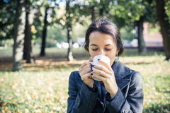 Laughing girl in an autumn part with a white cup of hot drink Royalty Free Stock Images
