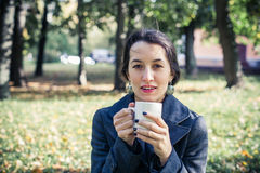 Laughing girl in an autumn part with a white cup of hot drink Stock Image