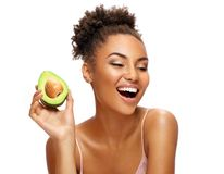 Laughing girl with avocado. royalty free stock image