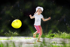 Laughing girl with baloon running under the sunlight Royalty Free Stock Image