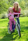 Laughing girl on bicycle with mother royalty free stock image