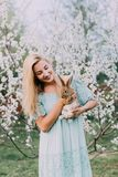 Laughing girl in a blue dress holding a rabbit in a white spring garden. royalty free stock images