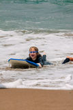 Laughing Girl On Boogie Board Washed Up On Beach Stock Photography