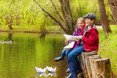 Laughing girl and boy near pond with paper boats Royalty Free Stock Photos