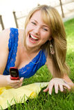 Laughing girl with a cellphone Stock Photos