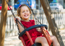 Laughing girl  on chain swing Royalty Free Stock Photo