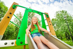Laughing girl on children chute ready to slide Stock Images