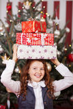 Laughing girl with Christmas gifts on her head Royalty Free Stock Image
