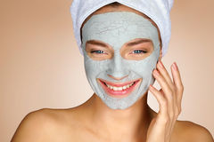 Laughing girl with clay facial mask. Stock Photos