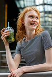 Laughing girl with curly red hair holding mojito and resting Stock Photo