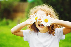 Laughing girl with daisy in her eyes. Laughing girl with daisy in her eyes in summer park Royalty Free Stock Images