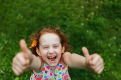 Little girl with daisy in her hairs, showing thumbs up. Laughing girl with daisy in her hairs, showing thumbs up Royalty Free Stock Photo