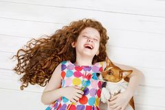 Laughing girl embracing the dog laying on a warm wooden floor royalty free stock photo