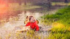 Laughing girl falling in puddle Stock Photos