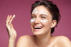 Laughing girl with flawless skin applying moisturizer cream on her face royalty free stock image