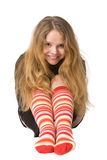 Laughing girl in funny socks. Laughing girl with long hair in long brown sweater and red-orange long socks sitting on the floor, isolated on white Royalty Free Stock Photo