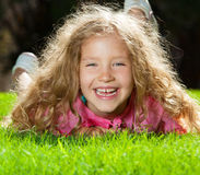 Laughing girl on grass Stock Images
