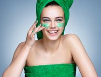 Laughing girl in green towels applying moisturizing cream on her face royalty free stock image