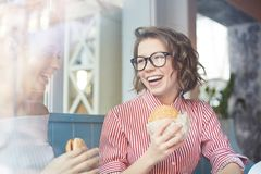 Break for snack. Laughing girl with hamburger and her friend having fun in fast food cafe after classes Stock Images