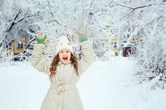Laughing girl with happy hand up, in winter park. Stock Images