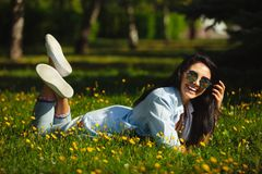 Laughing girl with happy smile lying on summer grass in circular sunglasses and bright clothes. Beautiful woman among the flower field stock images