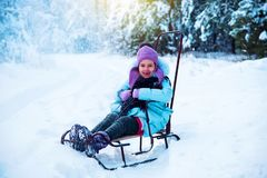 The laughing girl is happy in the winter, playing in the snow. royalty free stock image