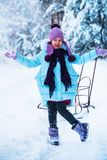 The laughing girl is happy in the winter, playing in the snow. royalty free stock images