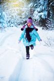The laughing girl is happy in the winter, playing in the snow. royalty free stock photo