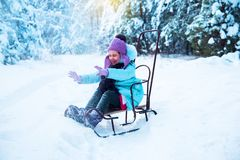 The laughing girl is happy in the winter, playing in the snow. stock photos