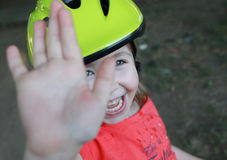 Laughing girl with helmet on head says stop or bye to camera Royalty Free Stock Images