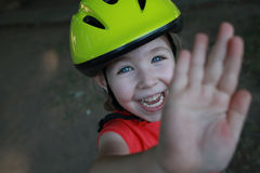 Laughing girl with helmet on head says stop or bye to camera Royalty Free Stock Image