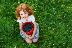 Laughing girl holding a bucket of berries Royalty Free Stock Photos