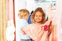 Laughing girl holds dress, boy behind her in shop Stock Photography