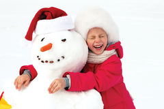 Laughing  girl hugging a snowman Royalty Free Stock Photo