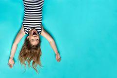 Laughing girl laying on blue backdrop up side down. Smiling, happy child. Childhood memories. Having fun. Joyful kid having great time in striped dress top royalty free stock photography