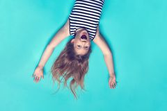 Laughing girl laying on blue backdrop up side down. Smiling, happy child. Childhood memories. Having fun. Joyful kid having great time in striped dress top stock photos