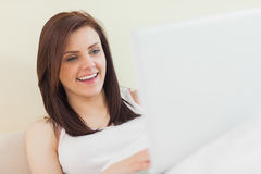 Laughing girl looking and using a laptop lying on a bed Royalty Free Stock Images