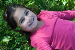 Laughing girl lying on the grass stock image