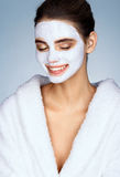 Laughing girl with moisturizing facial mask. Stock Image