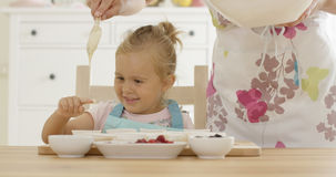Laughing girl with muffin cups and parent in apron Stock Photos