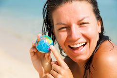 Girl with a globe in his hand. Closeup. Laughing girl on ocean background shows finger on small globe Stock Photography