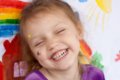 Laughing girl with paint on her face. Close up of laughing little girl with paint on her face Royalty Free Stock Photo