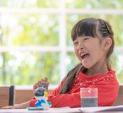 Laughing girl painting a doll in Art classroom, for creativit. Laughing girl is painting a doll in Art classroom, for creativity concept royalty free stock photos