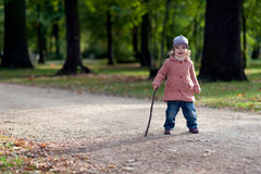 Laughing girl in a park. Laughing little girl with walking cane Royalty Free Stock Photography