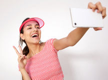 Laughing girl with peace hand sign taking selfie Royalty Free Stock Photography